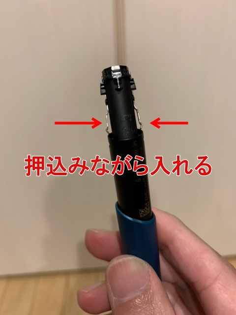 アイコス3DUO(デュオ)のキャップ内の黒いパーツのステンレス部分を押し込みながら入れる画像